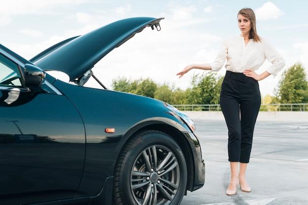 Vorderansicht der frau und des schwarzen autos Kostenlose Fotos