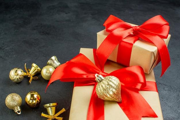 Vorderansicht der geschenkbox mit rotem band und dekorationszubehör auf dunklem hintergrund Kostenlose Fotos