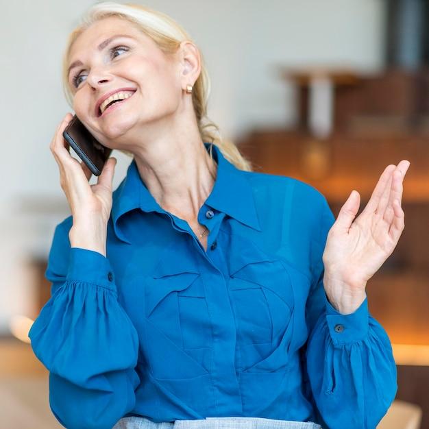 Vorderansicht der glücklichen älteren frau, die am telefon während der arbeit spricht Kostenlose Fotos