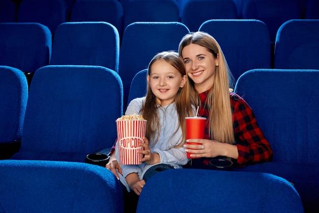 Vorderansicht der glücklichen familie, die zeit zusammen im leeren kino verbringt Kostenlose Fotos