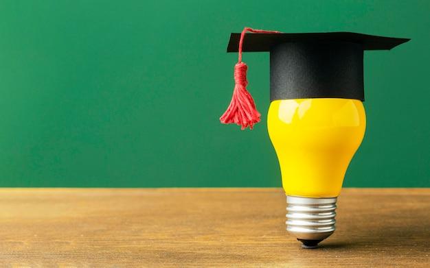 Vorderansicht der glühbirne mit akademischer kappe und kopienraum Kostenlose Fotos