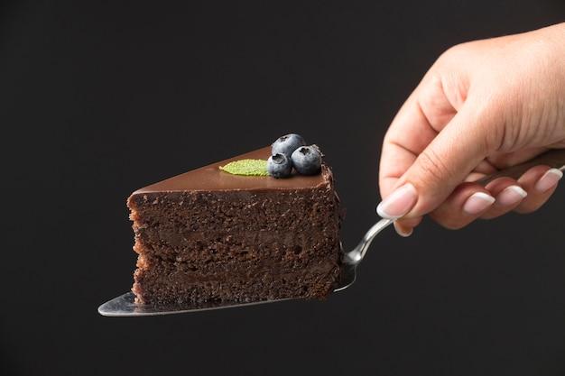 Vorderansicht der hand, die schokoladenkuchenscheibe hält Premium Fotos
