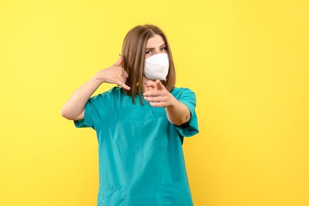 Vorderansicht der jungen ärztin mit maske auf gelber wand Kostenlose Fotos