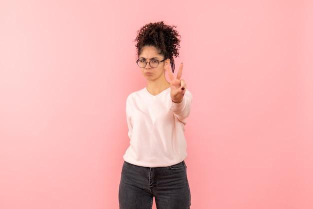 Vorderansicht der jungen frau, die nummer auf rosa wand zeigt Kostenlose Fotos