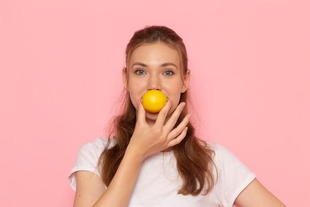 Vorderansicht der jungen frau im weißen t-shirt, das frische zitrone hält, die auf rosa wand lächelt Kostenlose Fotos