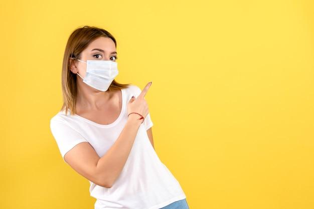 Vorderansicht der jungen frau in der maske auf einer gelben wand Kostenlose Fotos