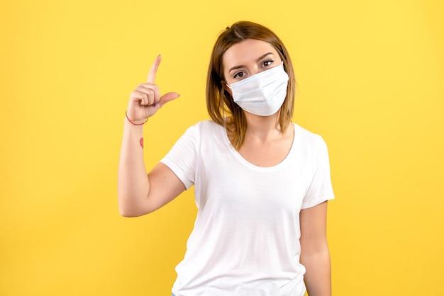 Vorderansicht der jungen frau in der sterilen maske auf gelber wand Kostenlose Fotos