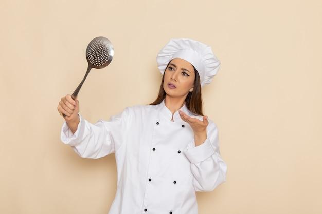 Vorderansicht der jungen köchin im weißen kochanzug, der riesigen silbernen löffel auf weißer wand hält Kostenlose Fotos