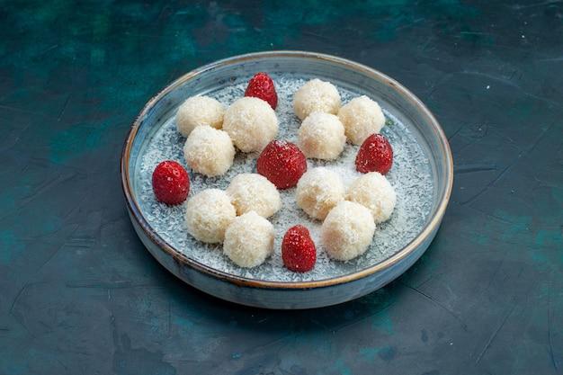 Vorderansicht der köstlichen kokosnussbonbons mit erdbeeren Kostenlose Fotos