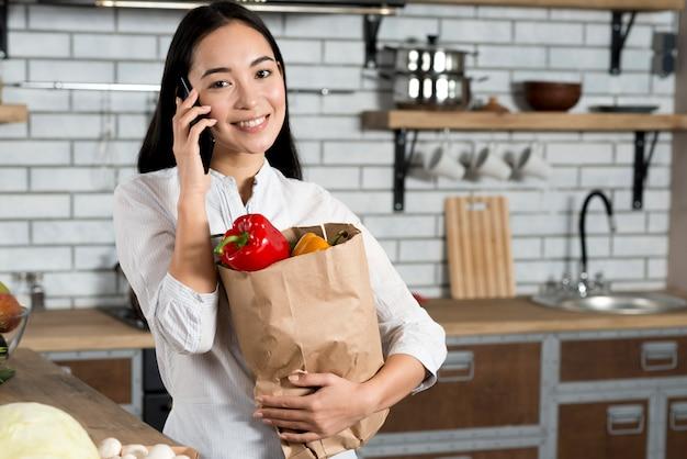 Vorderansicht der lächelnden asiatischen frau, die am handy beim halten der einkaufstüte spricht Kostenlose Fotos