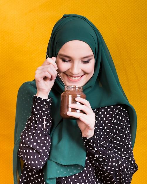 Vorderansicht der lächelnden frau schokoladenglas und löffel gegen gelben hintergrund halten Kostenlose Fotos