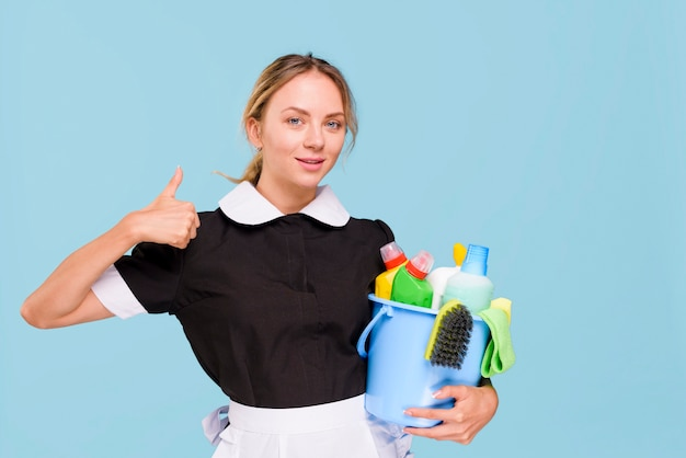 Vorderansicht der lächelnden hausmeisterfrau, die daumen herauf zeichen beim halten von reinigungsprodukten im eimer zeigt Kostenlose Fotos
