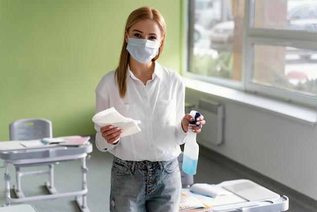 Vorderansicht der lehrerin mit desinfektionslösung im klassenzimmer Kostenlose Fotos