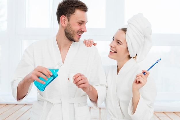 Vorderansicht der paare in den bademäntel mit mundwasser und zahnbürste Kostenlose Fotos