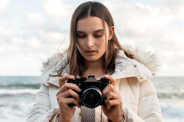 Vorderansicht der schönen frau mit kamera am strand Kostenlose Fotos
