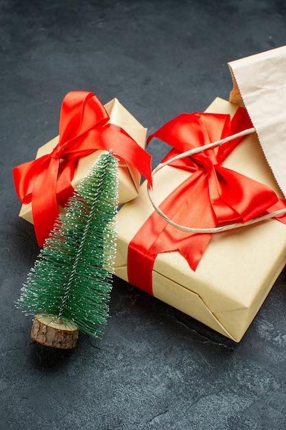 Vorderansicht der schönen geschenke mit rotem band und weihnachtsbaum auf einem dunklen tisch Kostenlose Fotos