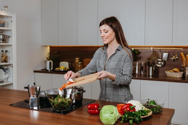 Vorderansicht der smiley-frau, die essen in der küche zu hause vorbereitet Kostenlose Fotos