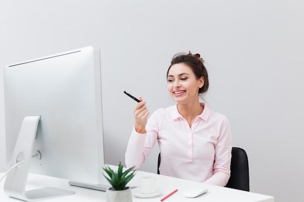 Vorderansicht der smileyfrau am schreibtisch stift auf den computer zeigend Kostenlose Fotos
