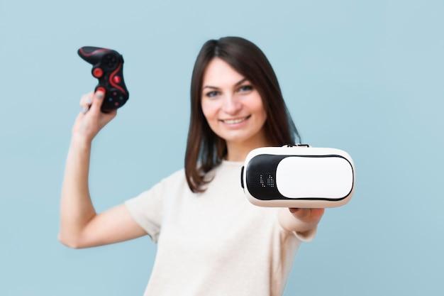 Vorderansicht der smileyfrau, die virtual-reality-headset hält Kostenlose Fotos