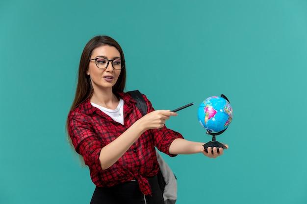 Vorderansicht der studentin, die rucksack hält, der kleinen globus und stift auf hellblauer wand hält Kostenlose Fotos