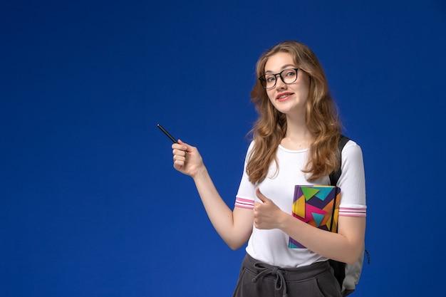 Vorderansicht der studentin im weißen hemd, das stift und heft auf dem blauen schreibtisch hält Kostenlose Fotos