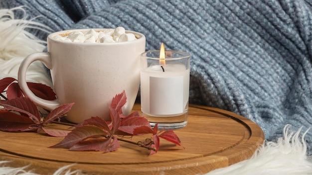 Vorderansicht der tasse heißen kakaos mit marshmallows und kerze Kostenlose Fotos