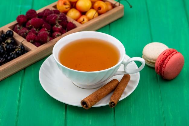 Vorderansicht der tasse tee mit zimt himbeeren schwarzen johannisbeeren weißen kirschen und macarons auf einer grünen oberfläche Kostenlose Fotos