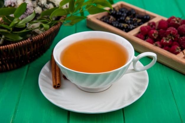 Vorderansicht der tasse tee mit zimthimbeeren und schwarzen johannisbeeren auf einer grünen oberfläche Kostenlose Fotos