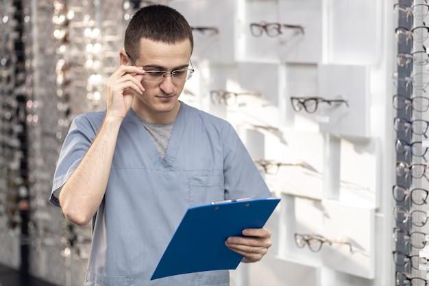 Vorderansicht der tragenden gläser des mannes und des betrachtens des notizblockes Kostenlose Fotos