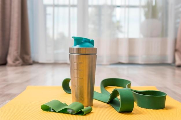 Vorderansicht der wasserflasche und des gummibands für das training zu hause Kostenlose Fotos