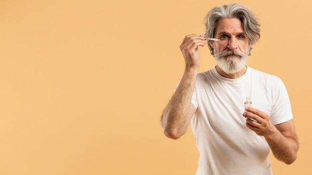 Vorderansicht des älteren bärtigen mannes, der serum anwendet Kostenlose Fotos