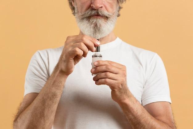Vorderansicht des älteren bärtigen mannes, der serum hält Kostenlose Fotos