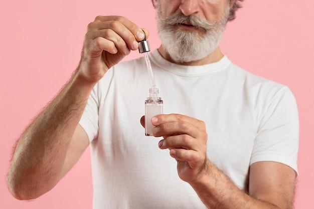 Vorderansicht des älteren bärtigen mannes unter verwendung des serums Kostenlose Fotos
