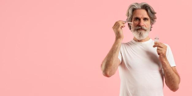 Vorderansicht des älteren mannes mit bart unter verwendung des serums Kostenlose Fotos