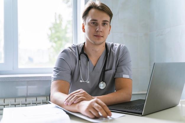 Vorderansicht des arztes mit stethoskop, das am laptop arbeitet Kostenlose Fotos