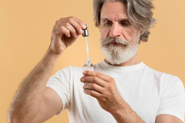 Vorderansicht des bärtigen älteren mannes, der serum hält Kostenlose Fotos