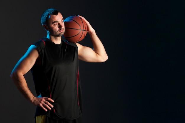 Vorderansicht des basketball-spielers mit ball auf schulter- und kopienraum Kostenlose Fotos