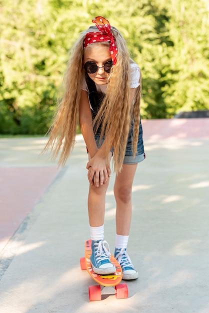 Vorderansicht des blonden mädchens auf skateboard Kostenlose Fotos