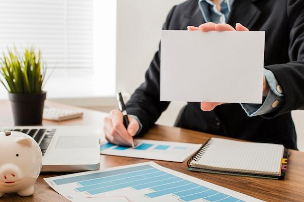 Vorderansicht des geschäftsmannes am büro, das leeres papier hält Kostenlose Fotos