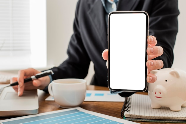 Vorderansicht des geschäftsmannes am büro, das leeres smartphone hält Kostenlose Fotos
