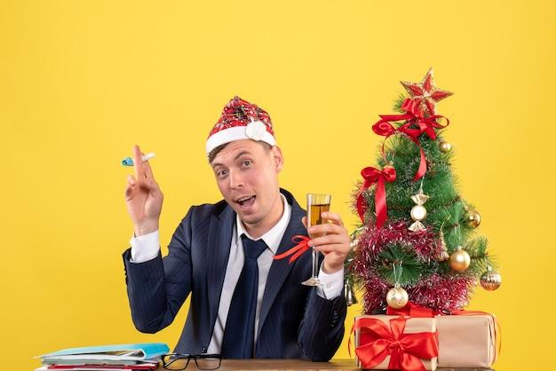 Vorderansicht des geschäftsmannes, der den krachmacher anstößt, der am tisch nahe dem weihnachtsbaum sitzt und auf gelb präsentiert Kostenlose Fotos