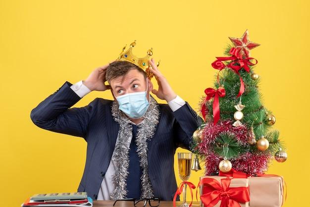 Vorderansicht des geschäftsmannes, der seine krone hält, die am tisch nahe weihnachtsbaum sitzt und auf gelb präsentiert Kostenlose Fotos