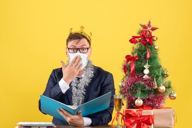Vorderansicht des geschäftsmannes mit der krone, die dokumentdatei hält, die am tisch nahe weihnachtsbaum und geschenken auf gelb sitzt Kostenlose Fotos