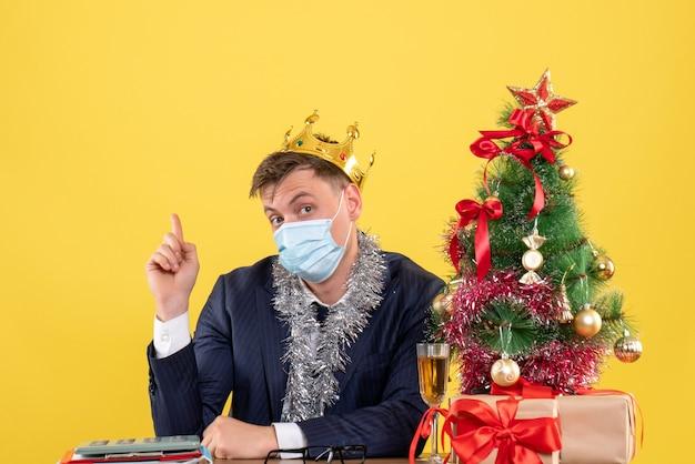 Vorderansicht des geschäftsmannes mit krone, die am tisch nahe weihnachtsbaum sitzt und auf gelb präsentiert Kostenlose Fotos