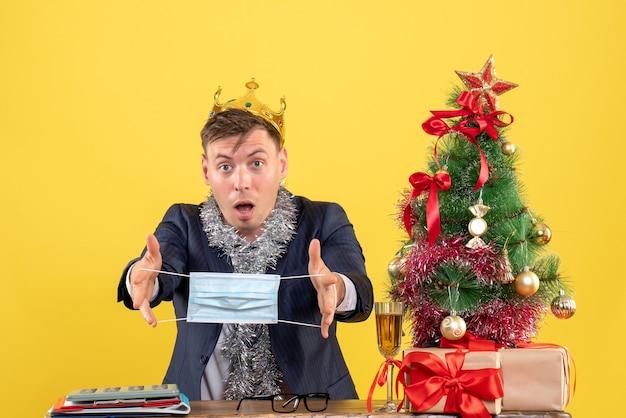 Vorderansicht des geschäftsmannes mit krone, die maske hält, die am tisch nahe weihnachtsbaum und geschenken auf gelb sitzt Kostenlose Fotos