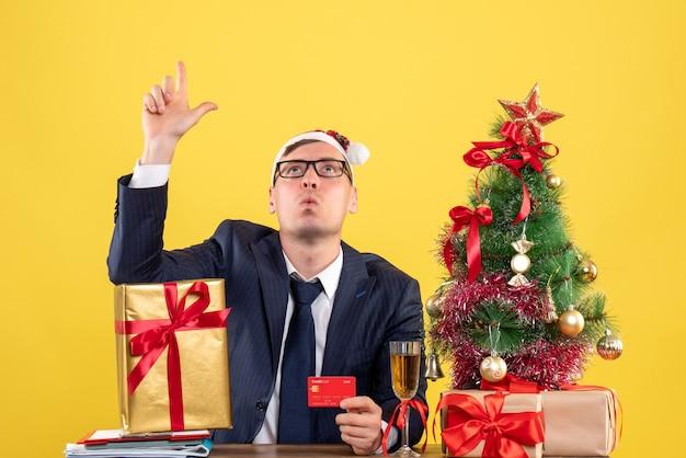 Vorderansicht des geschäftsmanns, der oben sitzt am tisch nahe weihnachtsbaum und geschenke auf gelb Kostenlose Fotos