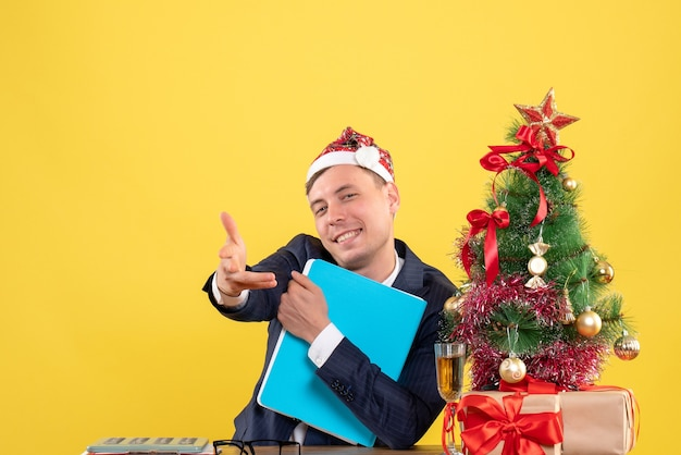 Vorderansicht des glücklichen geschäftsmannes, der hand gibt, die am tisch nahe weihnachtsbaum sitzt und auf gelb präsentiert Kostenlose Fotos