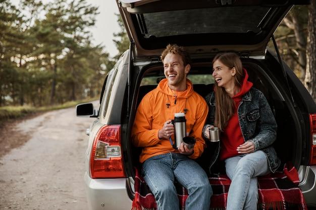Vorderansicht des glücklichen paares, das heißes getränk im kofferraum des autos genießt Kostenlose Fotos