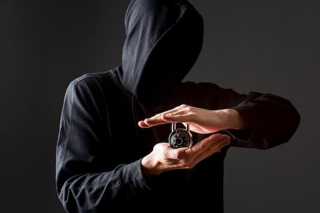 Vorderansicht des hackers, der schloss hält Kostenlose Fotos
