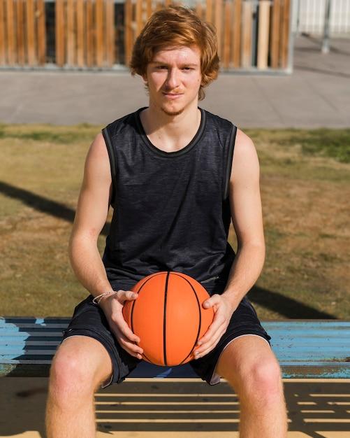 Vorderansicht des jungen, der einen basketballball hält Kostenlose Fotos